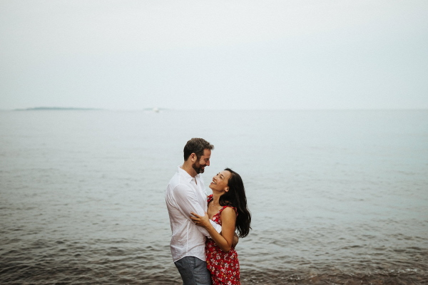 Man in white shirt and woman in red dress embrace by waters edge