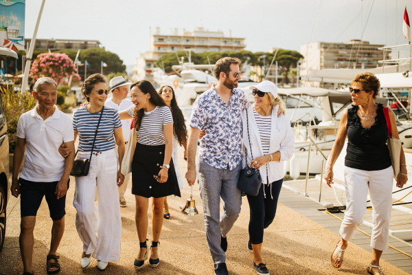 Friends and family walk together along yacht marina at Cote d'Azur France