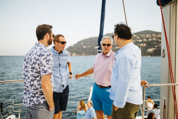 Men in the family gather to talk before nautical themed wedding on the deck of a yacht
