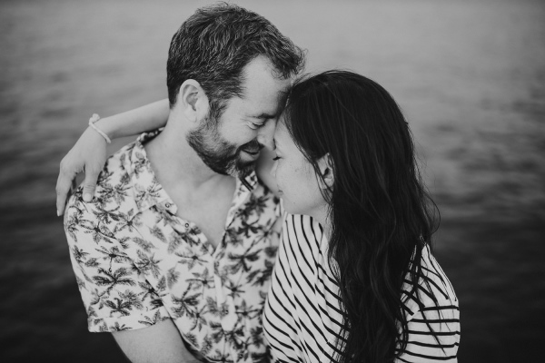 Black and white image of couple touch heads in warm embrace in floral and striped shirts