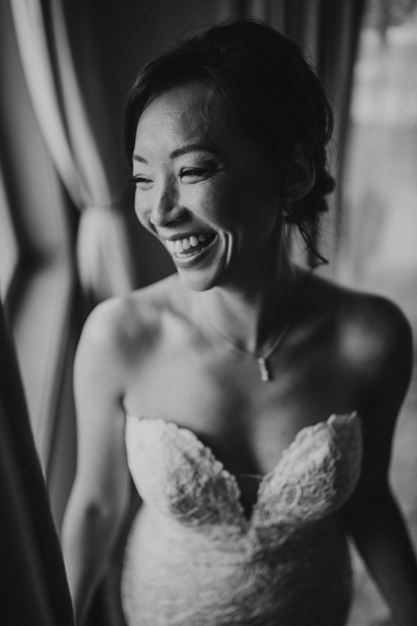 Black and white image of bride laughing while getting ready