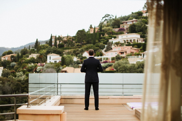 Groom in suit waiting for bride on balcony of hotel with back turned to camera