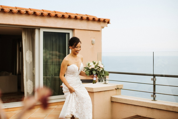 Bride approaches groom before wedding on balcony of hotel in white gown