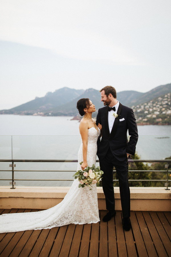 Bride and groom pose for photo in wedding outfits on balcony of hotel looking at each other