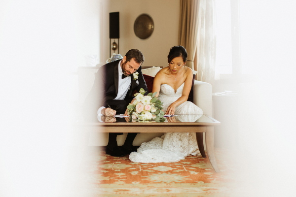 Bride and groom are photographed through door frame signing their wedding paperwork