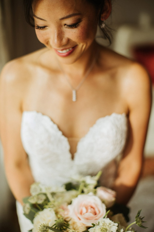 Close-up of bride looking down holding bouquet