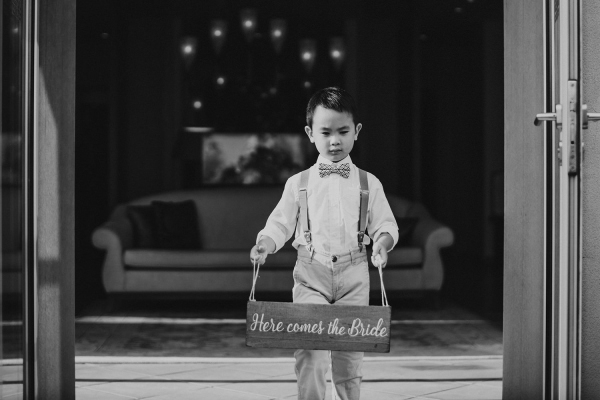 """Cute young boy carries wooden sign down aisle that reads """"Here comes the bride"""""""