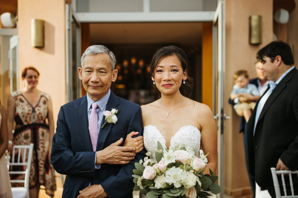 Bride walks down aisle on the arm of her father she wears a white strapless gown