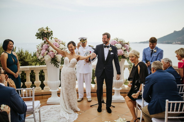 Couple just married throw arms up in air and look at friends and family