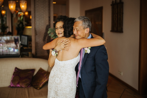 Bride hugs mother and father after the wedding