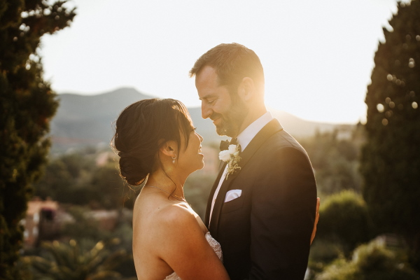 Mid-shot of bride and groom looking into each others eyes with sun shining through behind them