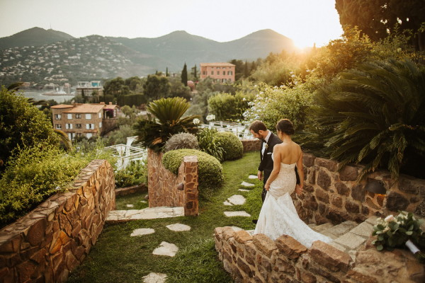 Bride in trailing dress and groom descend stairs into garden of hotel in France