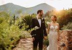 Husband and wife walk hand in hand in garden under setting sun