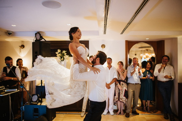 Groom lifts bride into the air as they take their first dance
