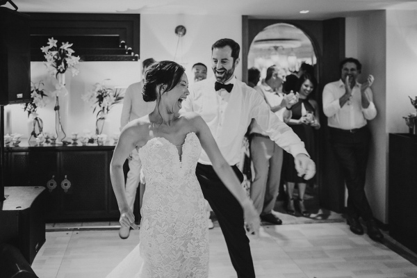 Black and white image of bride and groom dancing and smiling at wedding party