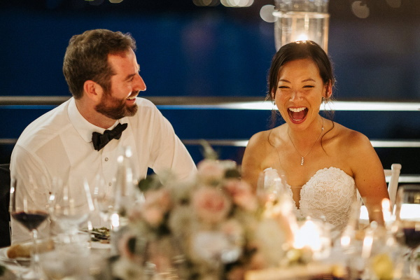 Bride and groom seated at wedding table laughing at speeches in the evening