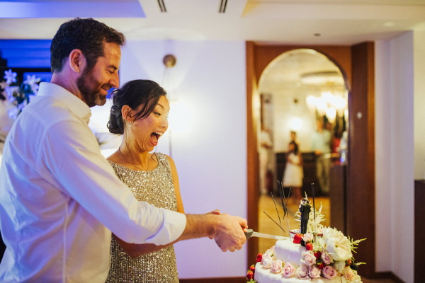 Bride and groom cut cake in going away outfits
