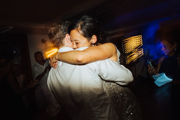 Bride and groom hug in the last moments of their wedding in going away outfits