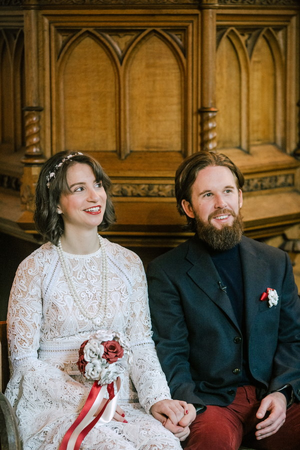 Bride and groom sit next to each other wearing black suit with black turtle neck and lace dress with pearl necklace and recycled paper bouquet
