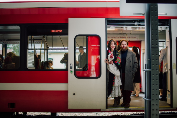 Bride and groom stand at the door of a red and white train in France which was caught to their sustainable wedding