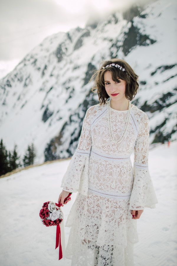 Bride in sustainable lace wedding dress with long bell sleeves and red lipstick stands in the snow in the French Alps