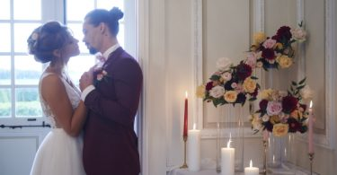 Bride and groom look into each others eyes framed by a window next to candle light