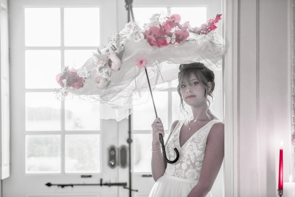 Bride holds white umbrella adorned with pink flowers and smiles at camera with french doors behind her
