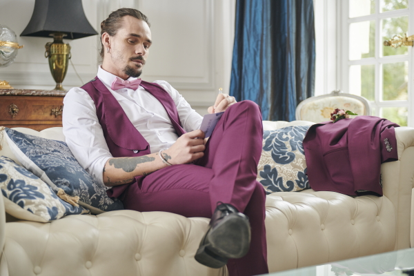 groom in purple suit with forearm tattoos writes his vows