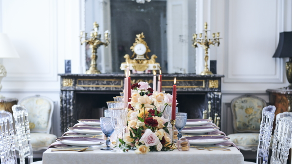 wedding table adorned with blue, burgundy and pink glasses, candles and floral arrangements