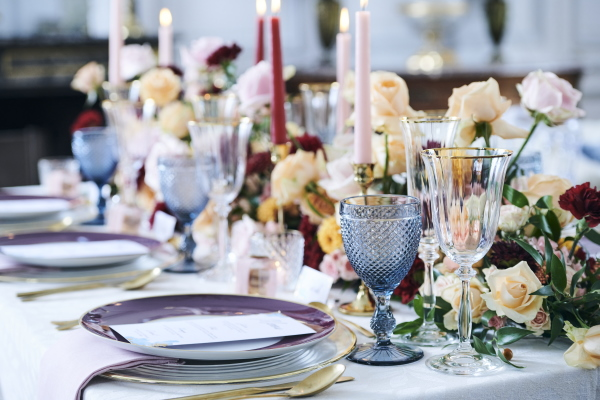 purple and gold rimmed plates and burgundy candles decorate the bridal table