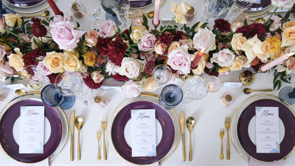 gold and purple plates, menu cards, burgundy floral arrangements at bridal table