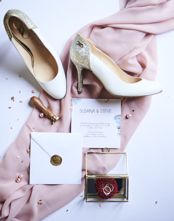 flatlay of diamante encrusted bridal shoes and wedding stationery