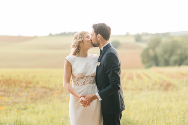 Bride and groom kiss in field in the grounds of Chateau d'Azy