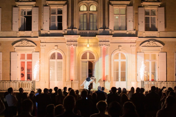 Wedding finale - bride and groom kiss in front of Chateau d'Azy with a spotlight on them in the evening and the silhouette of a crowd before them