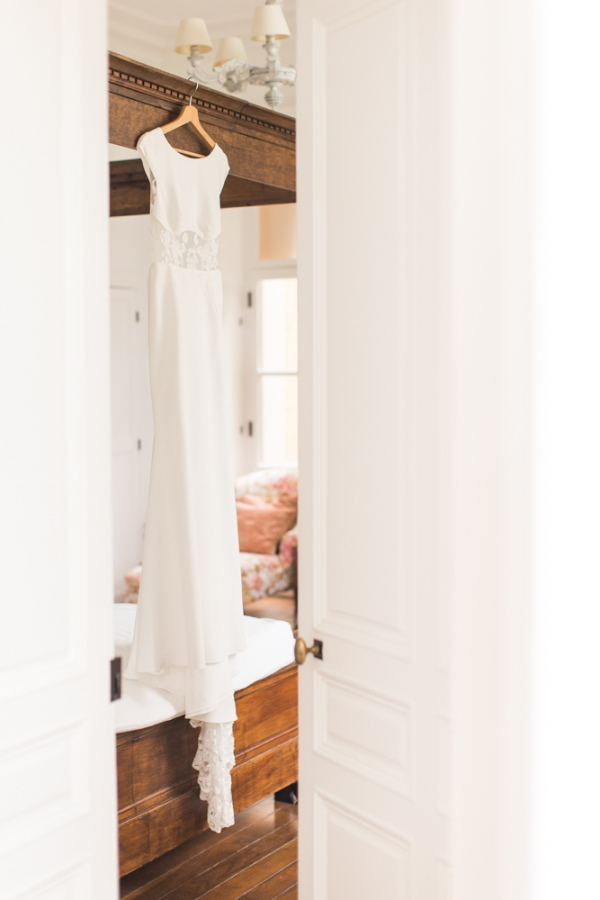 White and lace wedding dress hanging in doorway