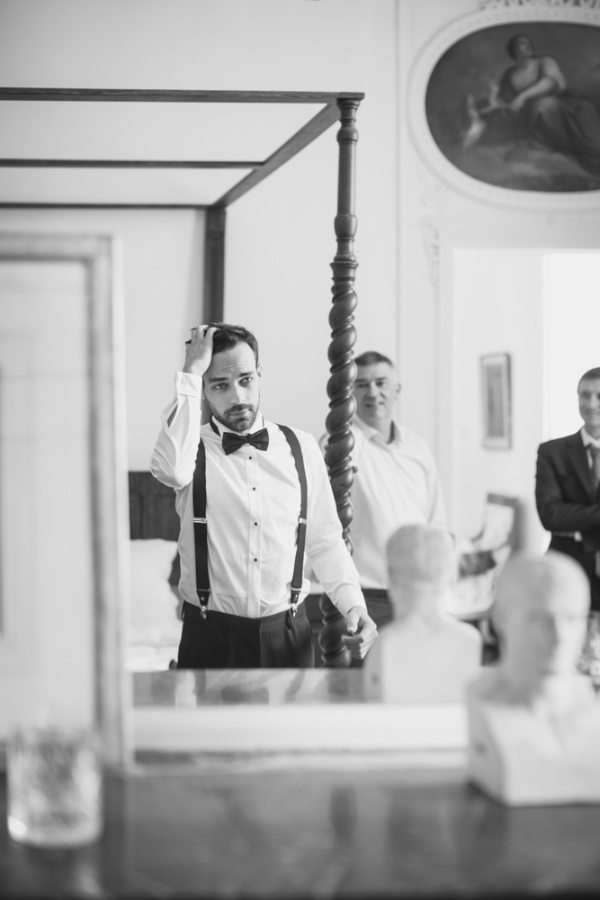 Groom doing his hair in his tuxedo before wedding