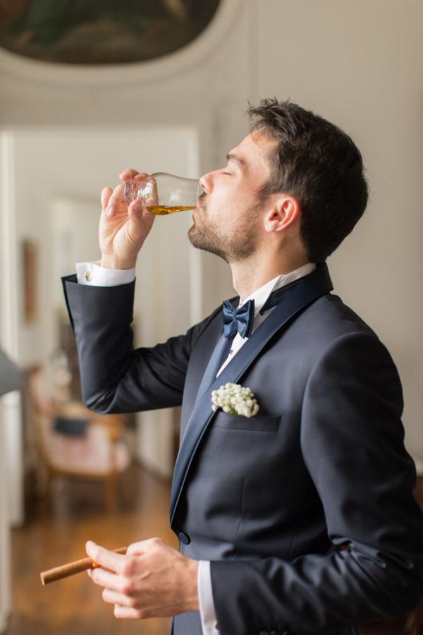Groom sips whiskey before wedding ceremony in tuxedo