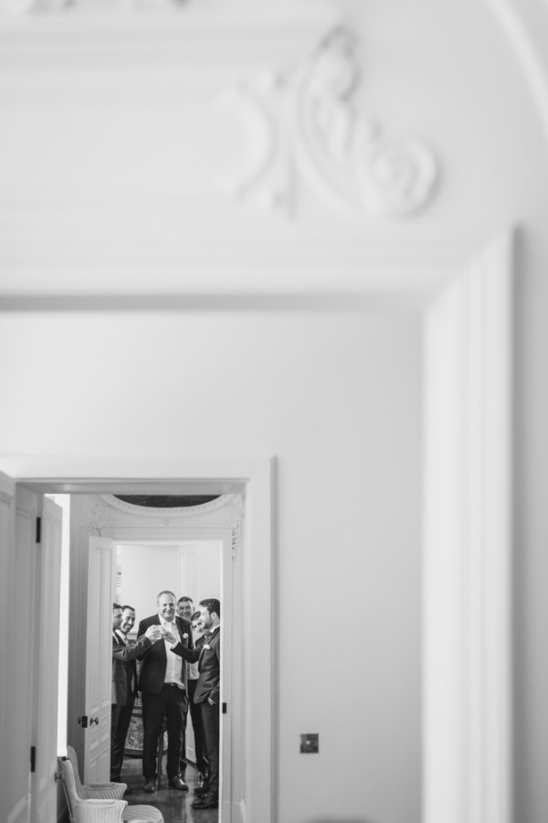 Groom and groomsmen in room at the end of the hall