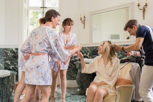 bride has drink with her bridesmaids in satin robes before wedding