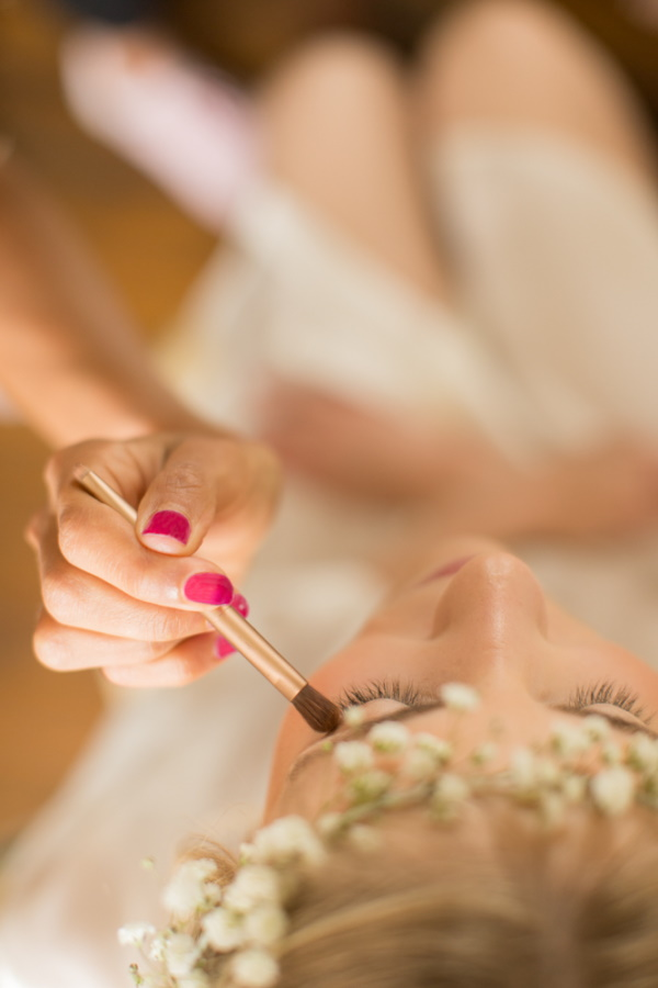 Image taken from above of bride having makeup done