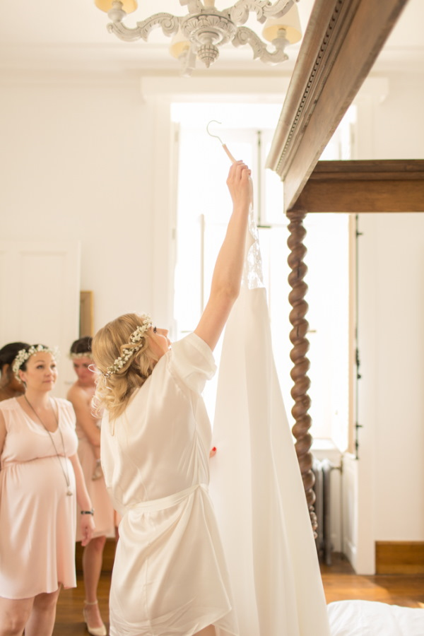 Bride reaches up to take wedding dress off hanger surrounded by bridesmaids