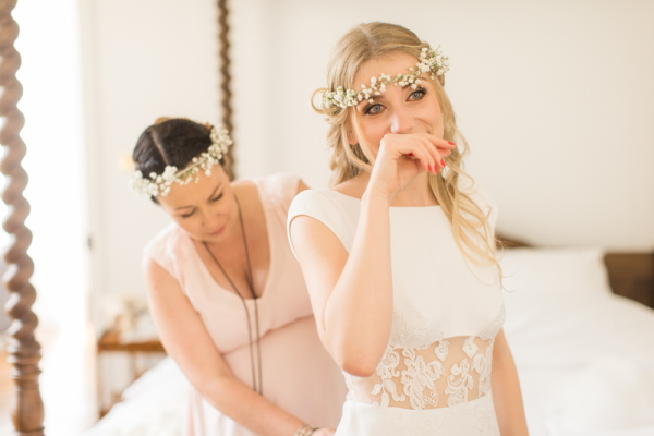 Bride is overcome with emotion as her bridesmaid does up her wedding dress