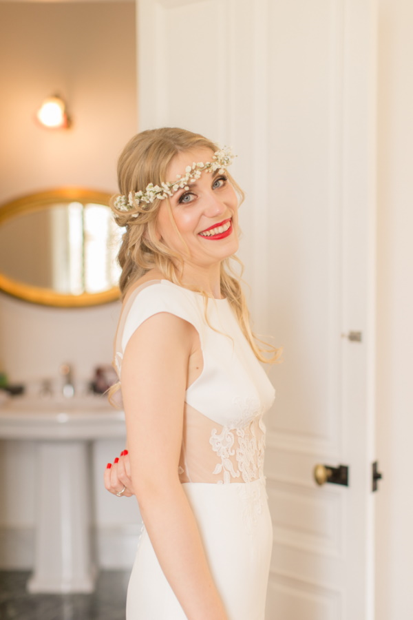 bride in red lipstick and flower crown smiles at camera