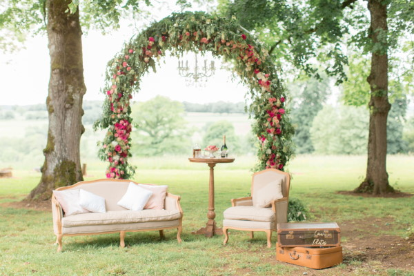 Floral arbor and comfortable lounging chairs in the garden for wedding at Chateau d'Azy