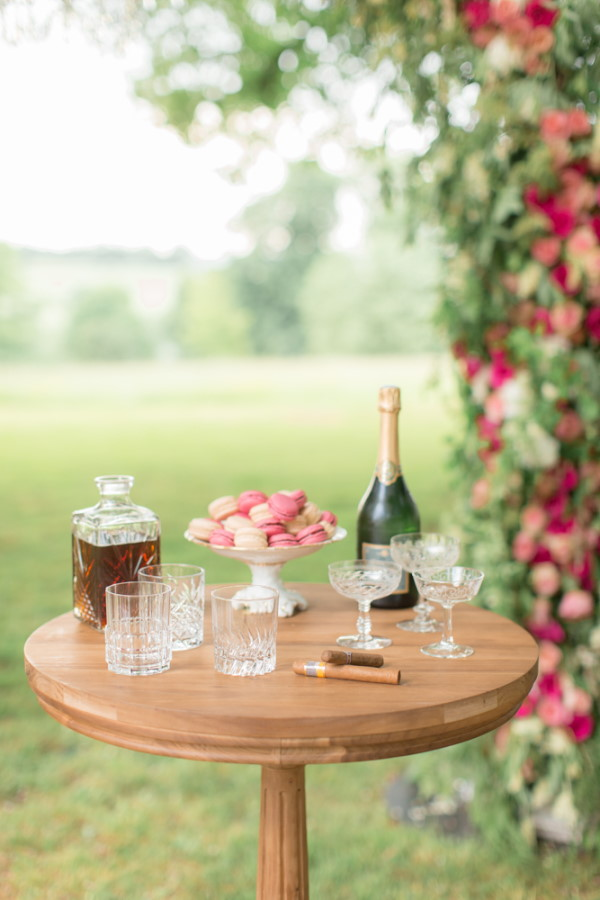 Small table with champagne and pink macarons for wedding guests