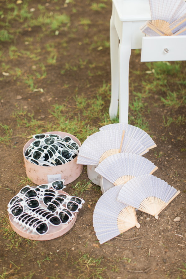 Sunglasses and fans await guests at wedding at Chateau d'Azy