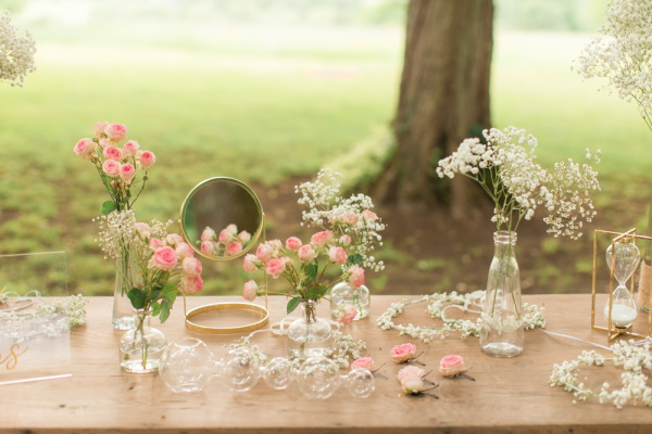 Small flower posies adorn the wedding bar in the garden on old wooden table