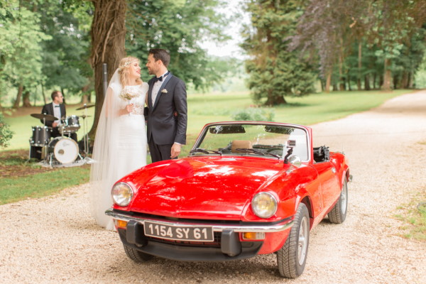 Bride and groom stand next to red vintage convertible car on the drive of Chateau d'Azy