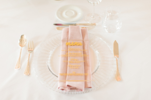 Table setting with pink napkin and clear and gold menu for wedding at Chateau d'Azy