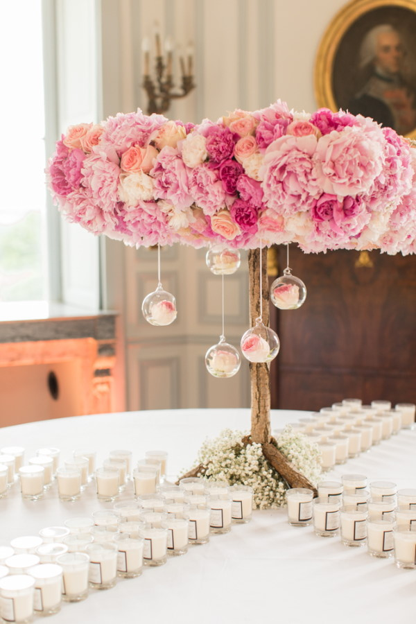 Pink rose tree with glass orbs hanging at centre of wedding favour table